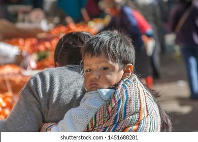 Peru, August 14, 2007: Child is being carried on its mother's back while she is shopping at a farm market.