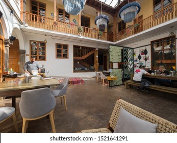 Peru, Cusco - September 18, 2019 - Selina Plaza de Armas Hostel dinning area, tourists sitting at the table and cashier in the background, colonial style decoration
