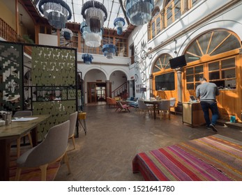 Peru, Cusco - September 18, 2019 - Selina Plaza de Armas Hostel restaurant area, sign on the wall blue lamps hang from ceiling