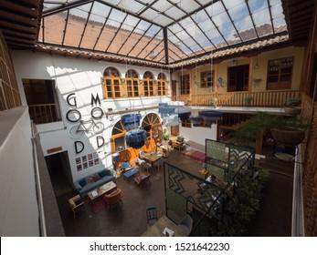 Peru, Cusco - September 18, 2019 - Selina Plaza de Armas Hostel, living area seen from above, blue sky through skylight glass