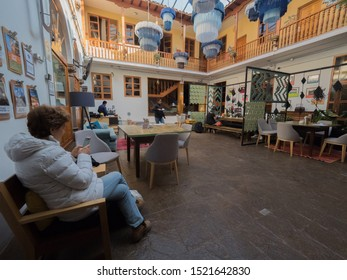 Peru, Cusco - September 18, 2019 - Selina Plaza de Armas Hostel, woman looks at cellphone, waitress carries a cup, gray chairs and blue lamps