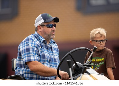 Peru, Indiana, USA - July 21, 2018 Father frives a tracktor with his son to his side at the Circus City Festival Parade