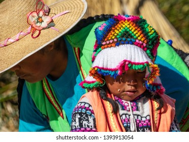 Peru, Lake Titicaca, on floating Islands Uros, the 9th of mai 2019. Little girl Amayra sitting on the reef floor.