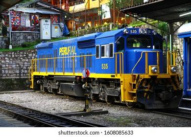 PERU RAIL TRAIN STATION, AGUAS CALIENTES, PERU - 25 March 2019. Symbolic Peru Rail locomotive is on the rails in the train station in Aguas Calientes.