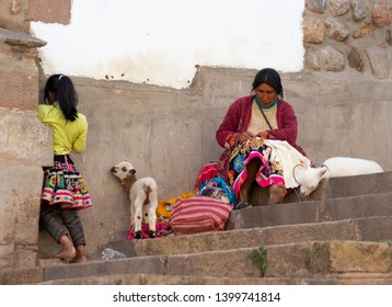 peru, in the streets of Cuzco 15th of April 2019. Peruvian mother with her child selling wooden articles. a little lamb plays with the child hide and seek.