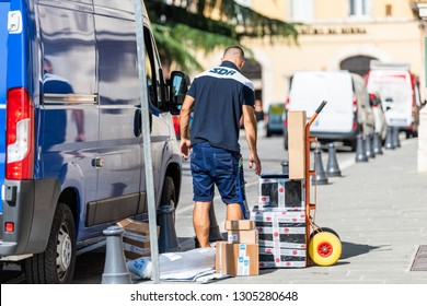 Perugia, Italy - August 29, 2018: Italian street outside in city sunny day with man worker delivery guy on road by truck and boxes