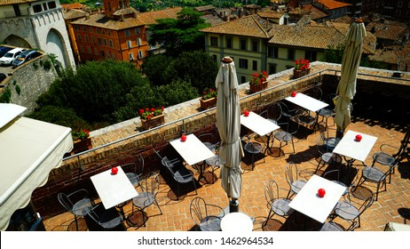 Perugia, Italy - July 21, 2018: Terrace of a restaurant with tables and umbrellas seen from above with the city of Perugia in the background
