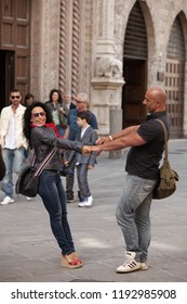 Perugia, Italy, May 13, 2013: Couple holding hands and posing for a photograph in the street in Perugia, Italy