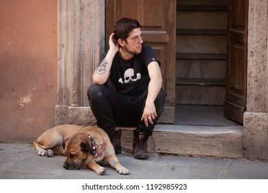Perugia, Italy, May 13, 2013: Man who appears to have an injured face sits on a doorstep with his dog in Perugia, Italy
