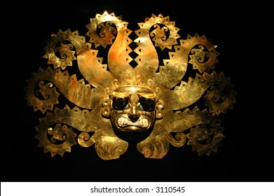 Peruvian ancient mask made out of gold with black background