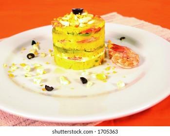 Peruvian causa limena dish with potato, egg and shrimp