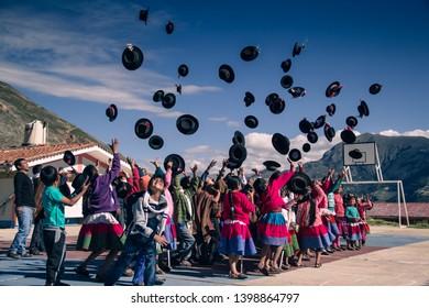 Peruvian children throwing hats to the sky. Carampa Ayacucho - Perú May 11 2016