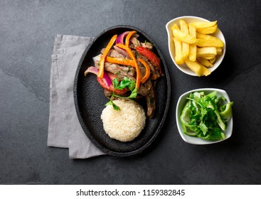 Peruvian dish Lomo saltado - beef tenderloin with purple onion, yellow chili, tomatoes served on black plate with french fries and rice. Top view