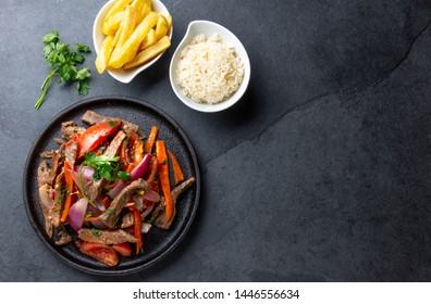 Peruanisches Gericht Lomo saltado - Rindfleischtenderloin mit violetter Zwiebel, gelbe Chilischoten, Tomaten auf schwarzem Teller mit Pommes frites und Reis serviert. Draufsicht