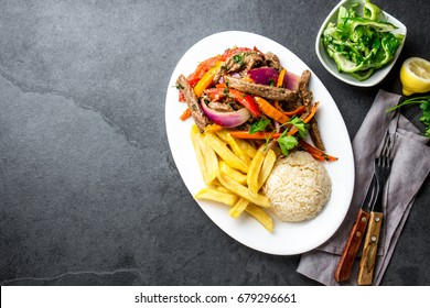 Peruvian dish Lomo saltado - beef tenderloin with purple onion, yellow chili, tomatoes served on white plate with french fries and rice. Top view