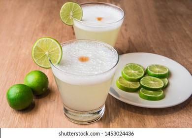 """Peruvian drink: """"Pisco Sour"""" with lemon on wooden background."""