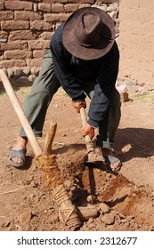 A peruvian farmer demonstrating how to prepare the land for farming