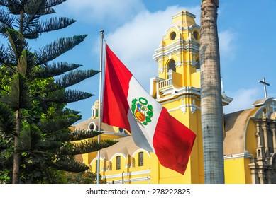 Peruvian flag and yellow church in the Barranco neighborhood in Lima, Peru