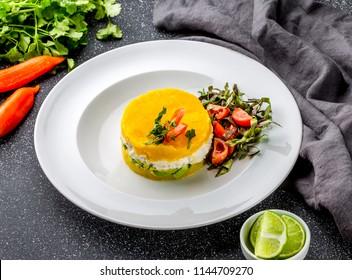 PERUVIAN FOOD. Causa rellena de pollo. Chicken causa rellena. Traditional peruvian dish from yellow potato, chicken, avocado on white plate.