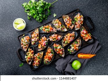 PERUVIAN FOOD. Choros a la chalaca. Big mussels, choros zapatos seasoned with purple onion, tomatoes, corn and lemon. Top view, black background. Traditional peruvian dish.
