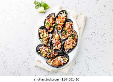PERUVIAN FOOD. Choros a la chalaca. Big mussels, choros zapatos seasoned with purple onion, tomatoes, corn and lemon. Top view, white background. Traditional peruvian dish.