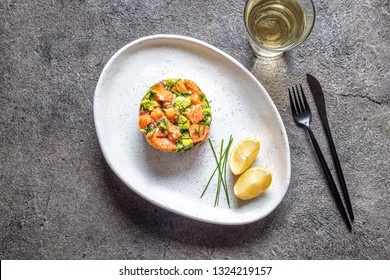 PERUVIAN FOOD. Salmon ceviche with avocado, spring onion and lemon on white plate served with white wine
