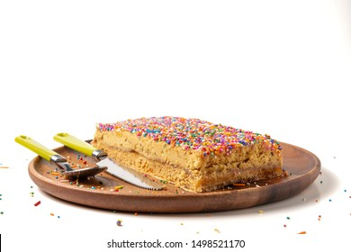 """Peruvian food: Turron """"Doña Pepa"""". Traditional dessert of Peru. Wooden plate and cutlery. White background."""