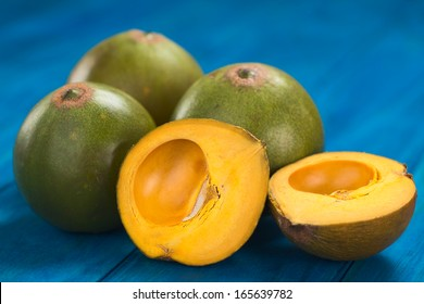 Peruvian fruit called Lucuma (lat. Pouteria lucuma) which has a dry, sweet flesh, and is mostly used to prepare yogurts, ice cream and other desserts (Selective Focus, Focus on the first lucuma half)