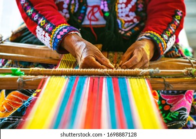 Peruvian indigenous Quechua woman weaving a textile with the traditional techniques in Cusco, Peru.