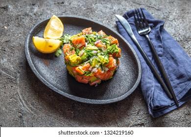 PERUVIAN NIKKEI FOOD. Salmon avocado ceviche on black plate, black background top view
