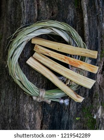 Peruvian Palo Santo holy wood incense sticks and Wildcrafted dried Sweetgrass (Hierochloe odorata) wrapped in organic cotton string on a tree bark in a forest preserve. Smudging ritual.