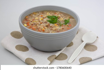 Peruvian quinoa soup with red rice and lentils in a gray clay bowl garnished with a leaf of green parsley
