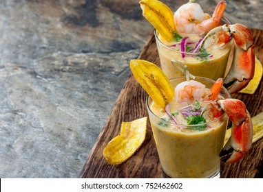 Peruvian seviche LECHE DE TIGRE. Raw fish cocktail ceviche with lime, grinder, chili and cilantro. Traditional peruvian food decorated with crabs, srimps and banana chips.