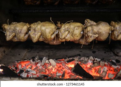 Peruvian style rotisserie chicken being roasted over a fire.