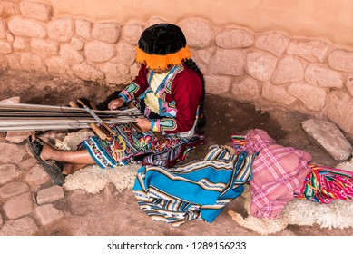 Peruvian women sitting on ground weaving with loom on her lap