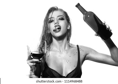 perverted fantasies. One pretty young sexy woman in black underwear with long wet hair holding wine bottle glass and cork in mouth standing in studio on white background, horizontal picture