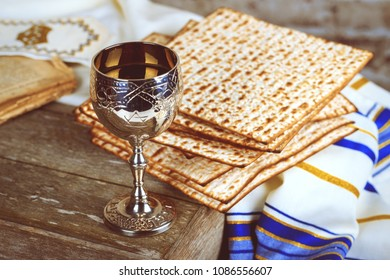 Pesach Passover symbols of great Jewish holiday. Traditional matzoh, matzah or matzo and wine in vintage silver plate and glass.