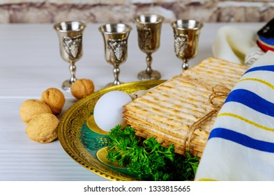 Pesach Passover symbols of great Jewish holiday. Traditional matzo and wine in vintage silver glass.