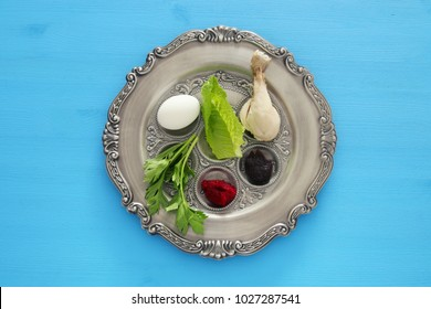 Pesah celebration concept (jewish Passover holiday). Traditional pesah plate with five symbols: horseradish, celery, egg, bone, maror, charoset