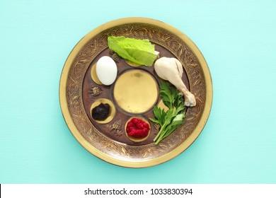 Pesah celebration concept (jewish Passover holiday). Traditional pesah plate with five symbols: horseradish, celery, egg, bone, maror, charoset