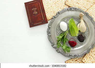 Pesah celebration concept (jewish Passover holiday). Traditional pesah plate with five symbols: horseradish, celery, egg, bone, maror, charoset. book with text in hebrew: Passover Haggadah