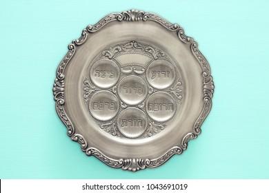 Pesah celebration concept (jewish Passover holiday). Traditional pesah plate text in hebrew: Passover, horseradish, celery, egg, bone, maror, charoset