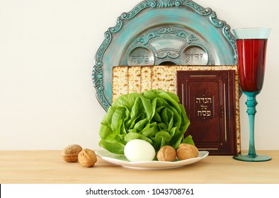 Pesah celebration concept (jewish Passover holiday). Translation for Hebrew Text: egg, bone. Traditional book with text in hebrew: Passover Haggadah (Passover Tale)