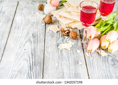 Pesah celebration concept. jewish Passover holiday background with matzo, eggs, spring flowers, wine, green background copy space top view