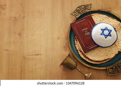 Pesah celebration concept (jewish Passover holiday). Translation for Hebrew Text over plate (Matzah) Matza and Traditional book with text in hebrew: Passover Haggadah (Passover Tale)