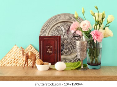 Pesah celebration concept (jewish Passover holiday). Traditional book with text in hebrew: Passover Haggadah (Passover Tale) and plate with word PASSOVER