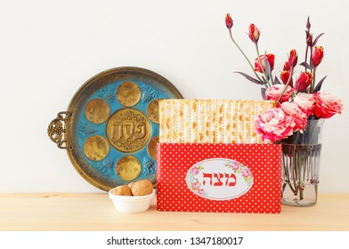 Pesah celebration concept (jewish Passover holiday). Translation for Hebrew Text over plate: (PESAH) PASSOVER, and Matzah utensils text: Matza