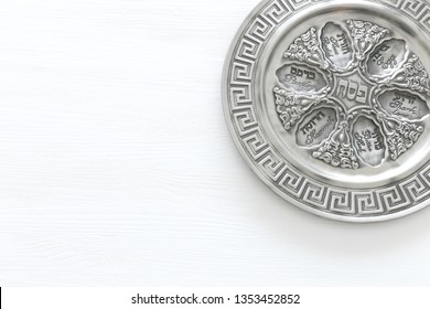 Pesah celebration concept (jewish Passover holiday). Translation for Hebrew Text over plate: (PESAH) PASSOVER. Top view flat lay
