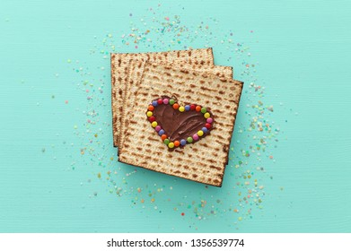 Pesah celebration concept (jewish Passover holiday) with chocolate heart and colorful candies over matzah. Top view flat lay