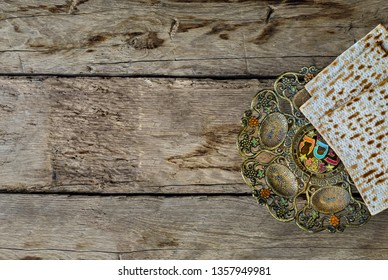 """Pesah celebration concept (Jewish Passover holiday). Vintage traditional seder plate and matzoh. In the central circle of the plate is written in Hebew """"Pesah"""" ."""